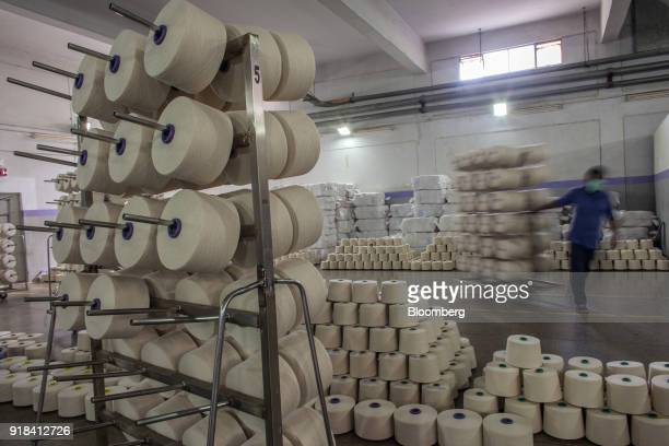 An employee transports cotton yarn cones on a trolley into the packing unit at the Artistic Denim Mills Ltd factory in Karachi Pakistan on Tuesday...