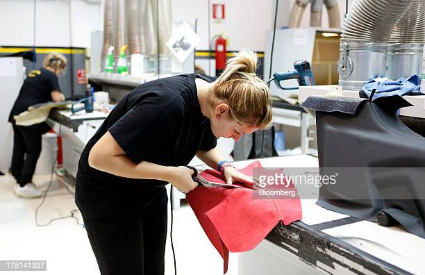 An employee trims a section of red leather as she prepares upholstery for the interior of a sports car at the Lamborghini SpA factory in Sant'Agata...