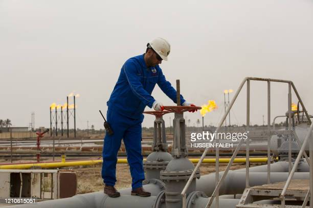 An employee turns a valve at the Nahr Bin Omar natural gas field, north of the southern Iraqi port of Basra on April 21, 2020.