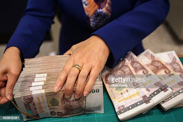 An employee unbinds bundles of onethousand baht banknotes inside a Bangkok Bank Pcl branch at the company's headquarters in Bangkok Thailand on...