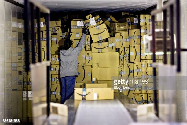 An employee unloads a truck load of Amazoncom Inc packages at the United Parcel Service Inc Chicago Area Consolidation Hub in Hodgkins Illinois US on...