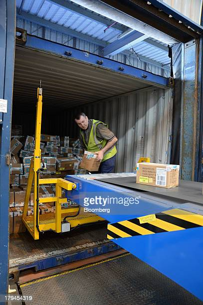 An employee unloads boxes of merchandise onto a conveyor belt at the Myer Holdings Ltd distribution center in Melbourne Australia on Tuesday Sept 3...