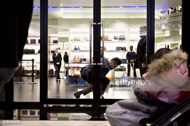 An employee unlocks the door of a Prada SpA store at the Fashion Outlets of Chicago mall in Chicago Illinois US on Thursday Nov 23 2017 The highly...