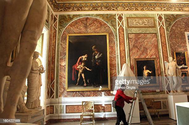 An employee unveils 'The Genius' a sculpture belonging to the Louvre museum in Rome for a temporary exhibition while paintings by Caravaggio are...