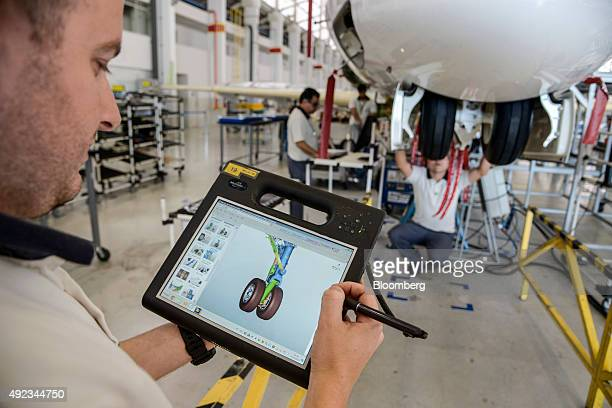 An employee uses a a tablet computer to view the landing gear of a Legacy 500 jet on the assembly line at the Embraer SA manufacturing plant in Sao...
