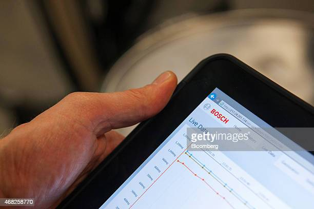 An employee uses a Bosch 40 app on a tablet device to control production on the automobile gasoline direct injector valve assembly line at the Robert...