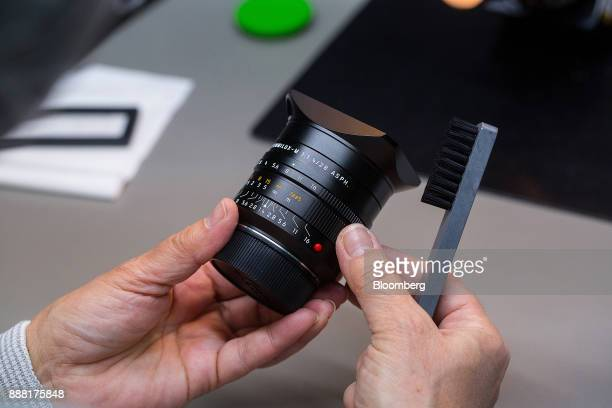 An employee uses a brush while carrying out final quality checks on a Leica SummiluxM 28 mm f/14 Aspherical lens at the Leica Camera AG factory in...
