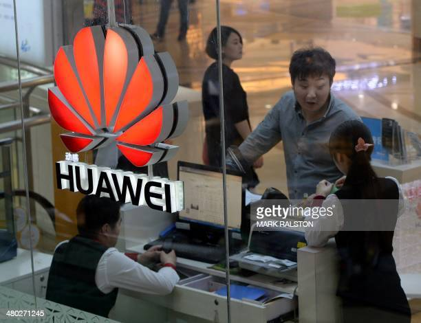 An employee uses a computer as she deals with a customer at a Huawei store in Beijing on March 24 2014 Chinese telecoms and Internet giant Huawei...