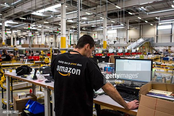 An employee uses a computer to process customer orders in the shipping zone of the new AmazonCom Inc fulfillment center on its opening day in...