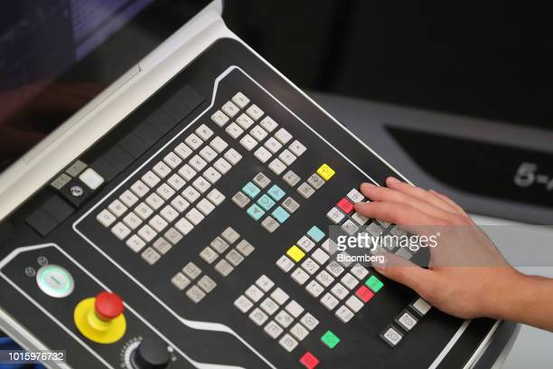 An employee uses a console control panel on the automobile axis turning and milling production line inside the Schaeffler AG machine tool 40 factory...