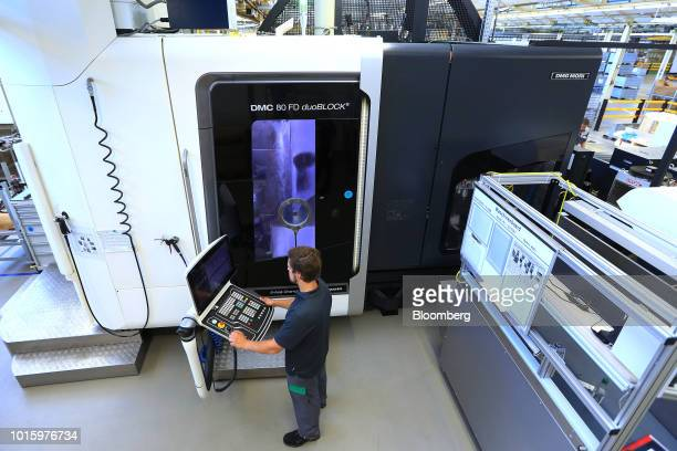 An employee uses a console control panel to operate a 5axis machining center manufactured by DMG Mori Co on the automobile axis turning and milling...