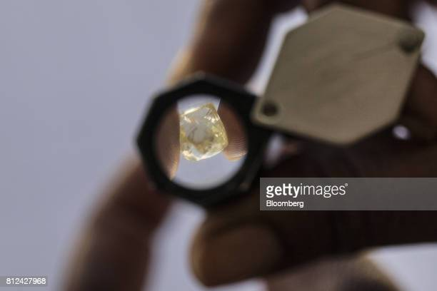 An employee uses a diamond loup to magnify a large rough diamond at the Namibian Diamond Trading Co diamond processing and valuation center a joint...