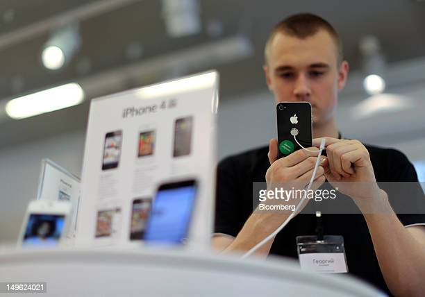 An employee uses a display model Apple Inc iPhone 4S inside a reStore a premium Apple product reseller in Moscow Russia on Wednesday Aug 1 2012 OAO...