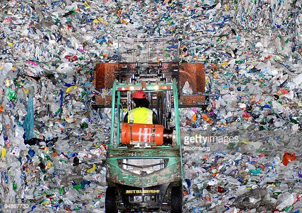 An employee uses a fork lift to move discarded plastic bottles ready for crushing and recycling at the Alternative Waste Solutions factory in...
