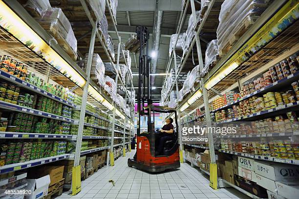 An employee uses a fork lift truck to restock high shelves with food products at an Arzan wholesale supermarket store in Almaty Kazakhstan on Friday...