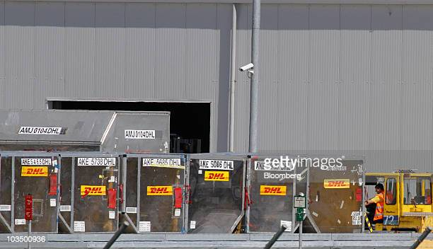 An employee uses a forklift to push DHL Worldwide Express air cargo containers at LeipzigHalle Airport in Leipzig Germany on Friday Aug 20 2010 With...