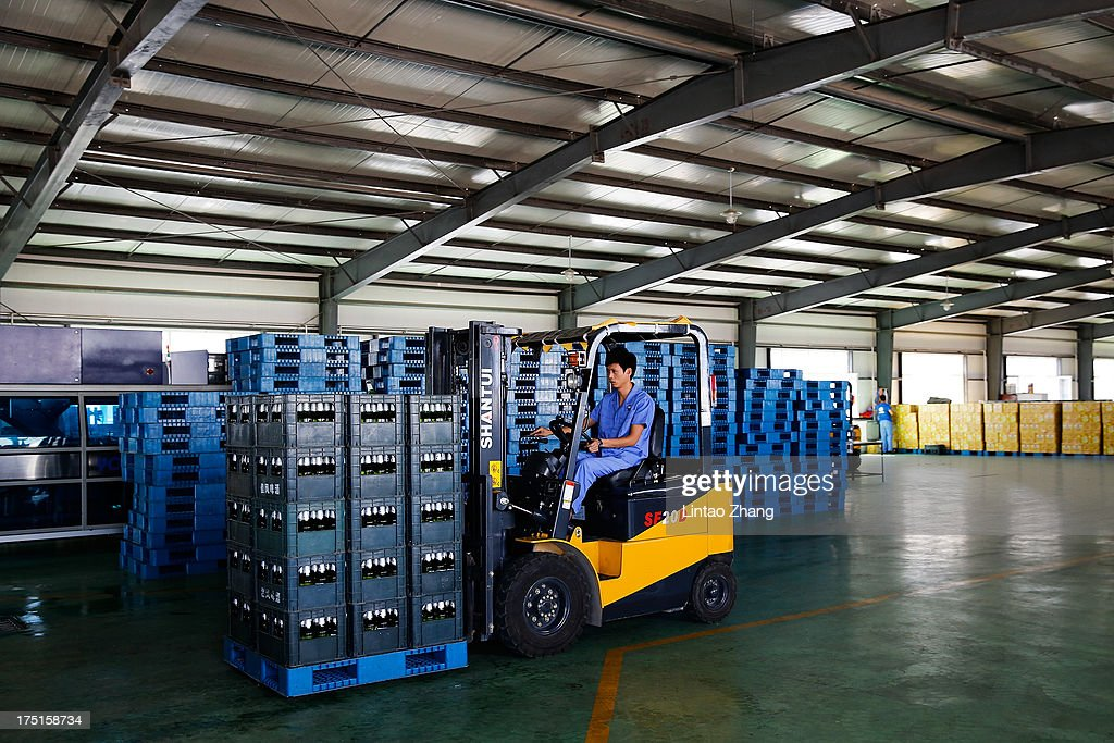 An employee uses a forklift to transport beer in the warehouse at the Jinzhu Manjiang beer factory on August 1, 2013 in Fujin, Heilongjiang Province, China. Recent significant sustained high temperatures in China are expected to push beer industry volume and revenue growth up significantly.