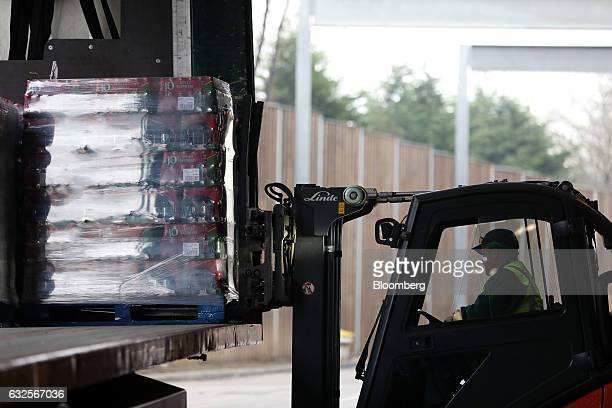An employee uses a forklift truck to lift a pallet of J2O fruit drinks into a delivery vehicle at the Britvic Plc factory and warehouse in Leeds UK...