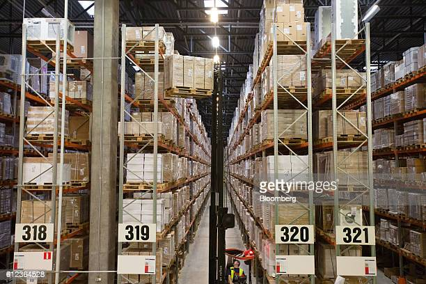 An employee uses a forklift truck to move goods from high level shelving in a storage aisle at the Ikea AB distribution center in Yesipovo village...