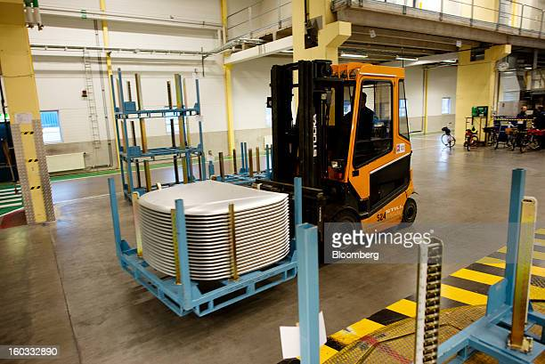 An employee uses a forklift truck to move spare body parts for Saab cars at the Saab Automobile plant owned by National Electric Vehicle Sweden AB in...
