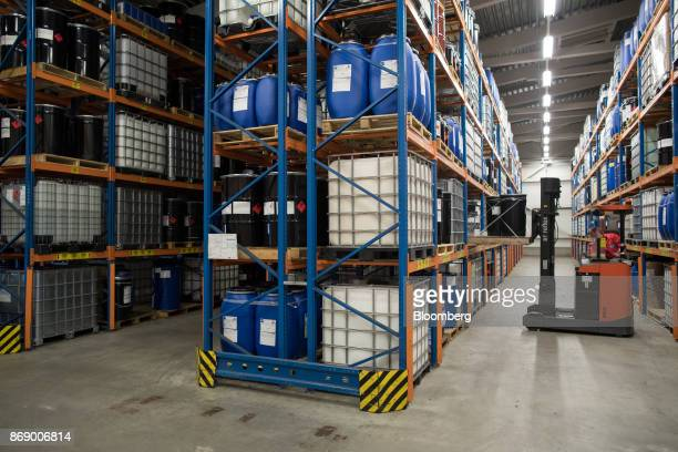 An employee uses a forklift truck to place chemical barrels onto storage racks at the Stahl Holdings BV headquarter factory in Waalwijk Netherlands...