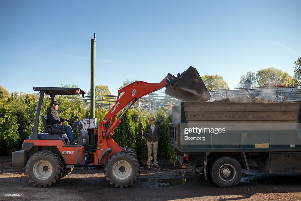 An employee uses a front loader to fill a dump truck with