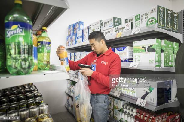 An employee uses a handheld computer to scan a bottle of orange juice while fulfilling an electronic order in a WalMart Stores Inc miniwarehouse for...