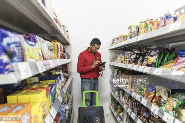 An employee uses a handheld computer while fulfilling an electronic order in a WalMart Stores Inc miniwarehouse for the company's onehour delivery...