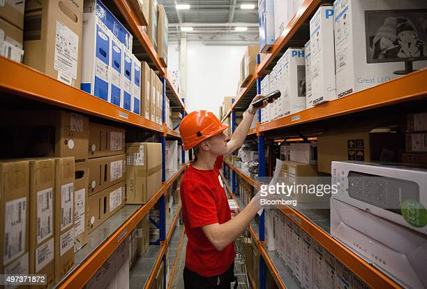 An employee uses a handheld scanner to register outgoing stock inside the warehouse of an order fulfillment centre operated by Ulmart in Saint...