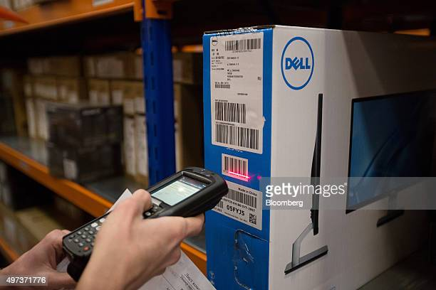An employee uses a handheld scanner to register the barcode of an outgoing Dell Inc computer monitor inside the warehouse of an order fulfillment...