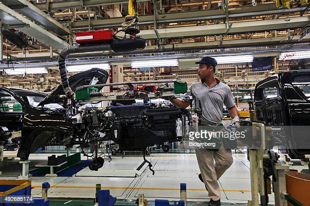 An employee uses a hoist crane to move the dashboard of a Toyota Motor Corp Hilux pickup truck on the production line at the company's plant in Ban...