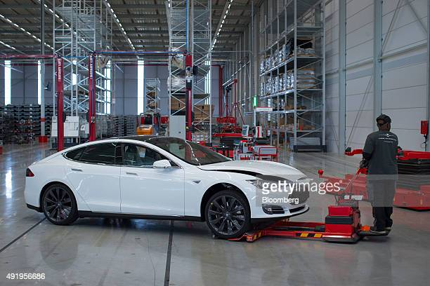 An employee uses a hydraulic hand truck to maneuver a Tesla Model S automobile ahead of final assembly at the Tesla Motors Inc factory in Tilburg...