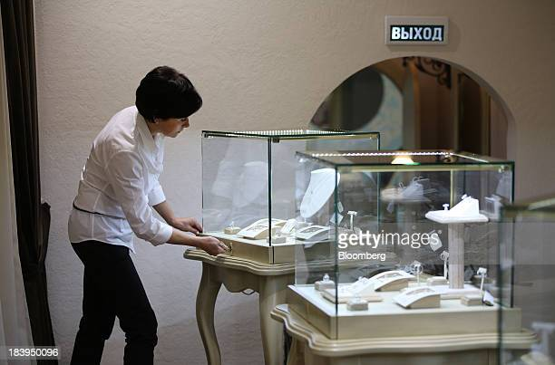 An employee uses a key to lock a glass case containing diamond jewelry for sale inside a luxury jewelry store operated by Kristall Production Corp in...