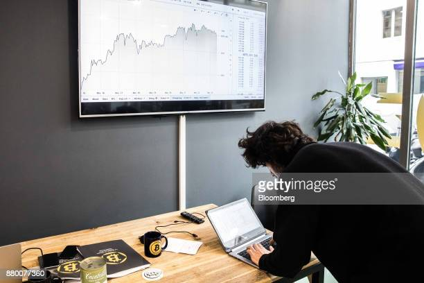 An employee uses a laptop computer as a screen displays a euro currency exchange graph inside the offices of La Maison du Bitcoin bank in Paris...
