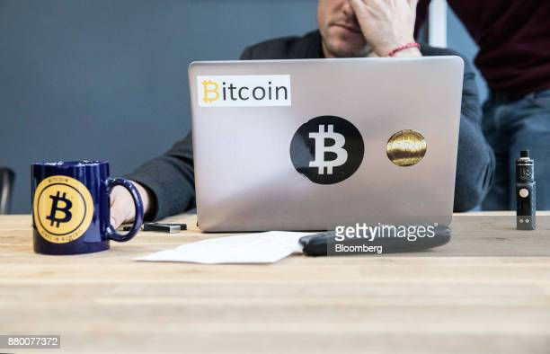 An employee uses a laptop computer branded with bitcoin logos inside the offices of La Maison du Bitcoin bank in Paris France on Thursday Nov 23 2017...