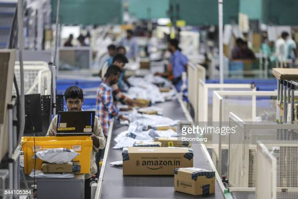 An employee uses a laptop computer while packages move along a conveyor belt at the Amazoncom Inc fulfillment center in Hyderabad India on Thursday...