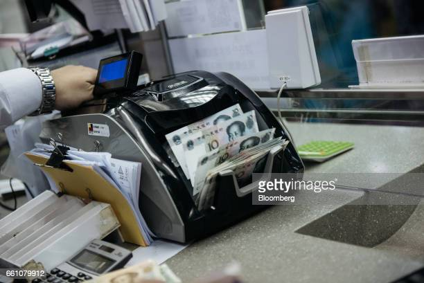 An employee uses a machine to count Chinese ten yuan banknotes at the Professional Foreign Currency Exchange Ltd store in Hong Kong China on Thursday...