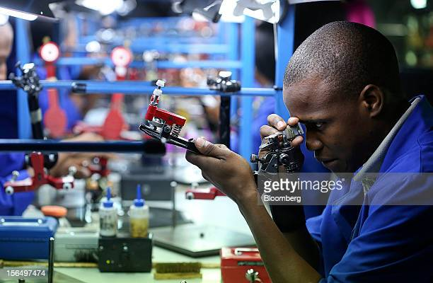 An employee uses a machine to inspect a diamond before the final stages of polishing at the Shrenuj Botswana Ltd sightholder office in Gaborone...