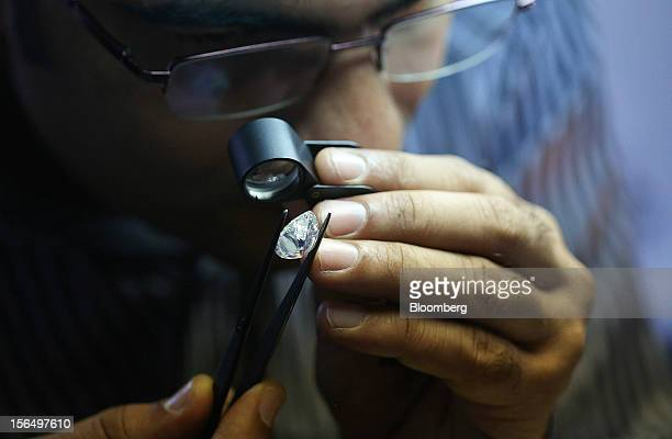 An employee uses a magnifier to inspect a finished pearshaped diamond before final classification at the Shrenuj Botswana Ltd sightholder office in...