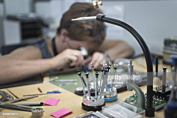 An employee uses a magnifying eyepiece to adjust the mechanism of a wristwatch at the Zenith a watchmaking unit of LVMH Moet Hennessy Louis Vuitton...