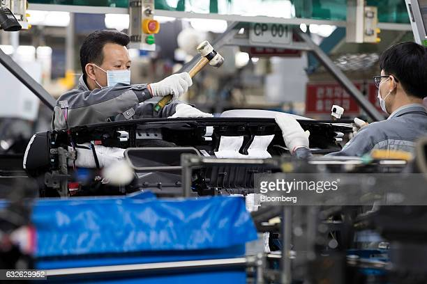 An employee uses a mallet while assembling a vehicle dashboard module on a production line at the Hyundai Mobis Co factory in Asan South Chungcheong...