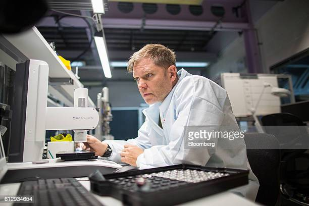An employee uses a microscope to check the quality of an impeller for a digital motor inside the motors build lab at the Dyson Ltd campus in...