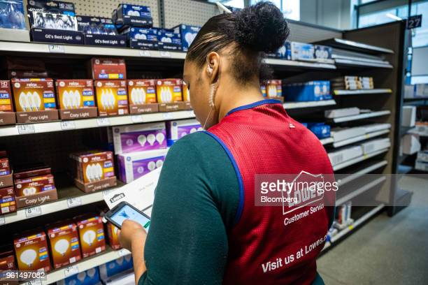 An employee uses a mobile device to check an online order at a Lowe's Cos store in New York US on Tuesday May 22 2018 Lowe's Cos is scheduled to...
