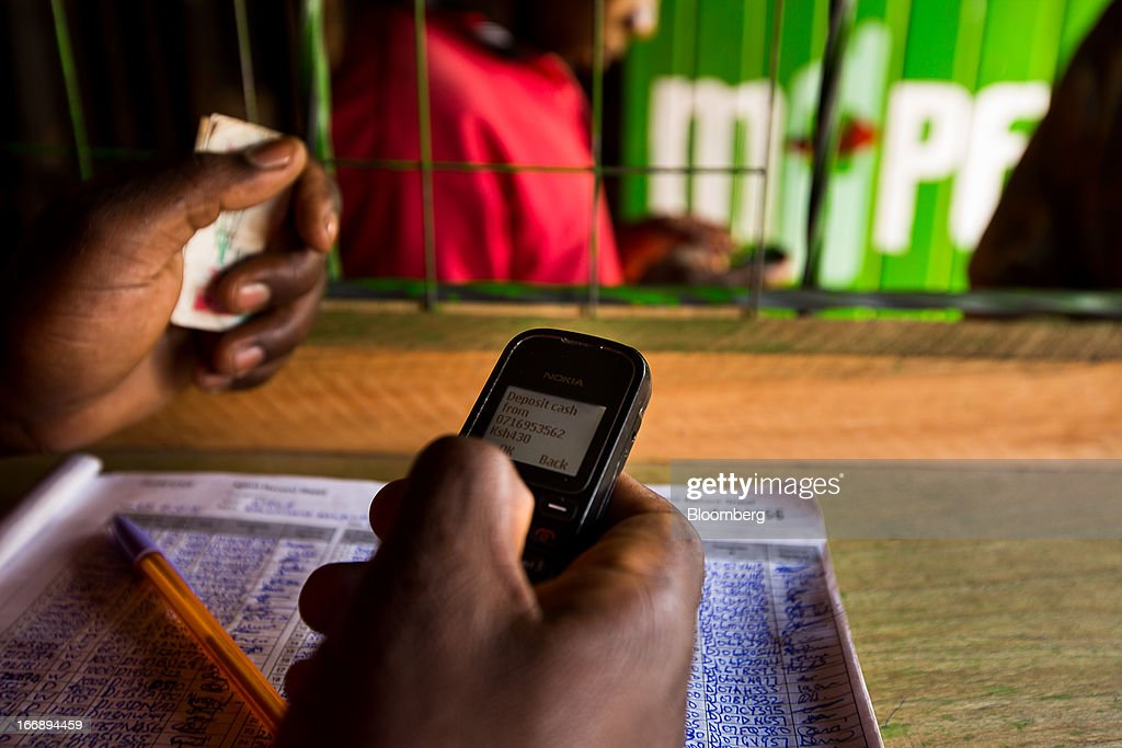 An employee uses a Nokia 1200 mobile phone inside an M-Pesa store in Nairobi, Kenya, on Sunday, April 14, 2013. In the six years since Kenya's M-Pesa brought banking-by-phone to Africa, the service has grown from a novelty to a bona fide payment network. Photographer: Trevor Snapp/Bloomberg via Getty Images