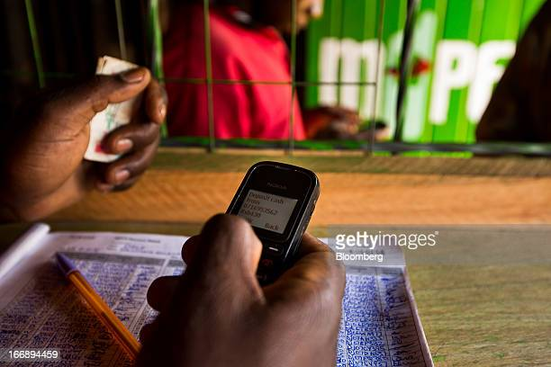 An employee uses a Nokia 1200 mobile phone inside an MPesa store in Nairobi Kenya on Sunday April 14 2013 In the six years since Kenya's MPesa...