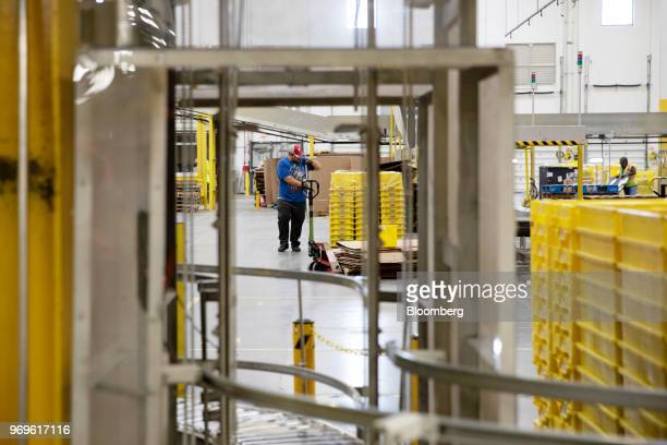 An employee uses a pallet jack to transport plastic crates at the Amazoncom Inc fulfillment center in Robbinsville New Jersey US on Thursday June 7...