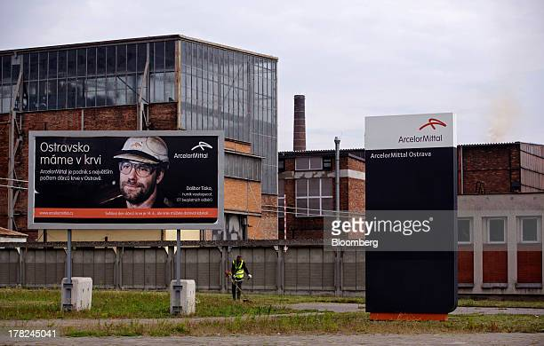 An employee uses a petrol strimmer to cut grass near a sign outside ArcelorMitta's steel plant in Ostrava, Czech Republic, on Monday, Aug. 26, 2013....