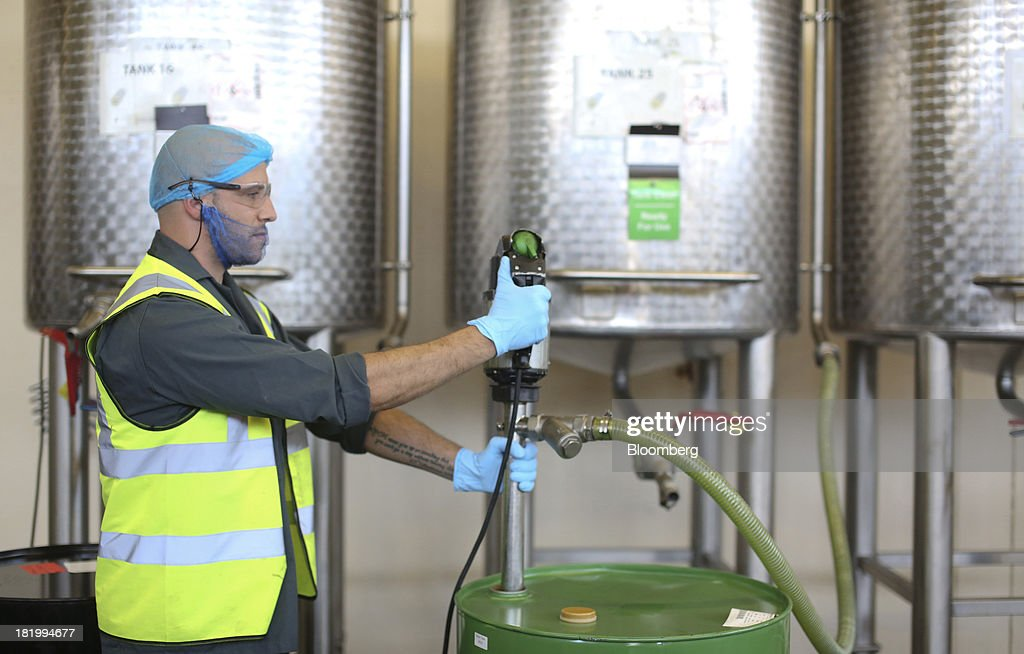 An employee uses a pump to pour a flavoring into a container drum at the Treatt Plc factory in Bury St Edmunds, U.K., on Wednesday, Sept. 25, 2013. Treatt Plc, the U.K. supplier of mango oil to the Body Shop, is considering the biggest investment splurge in its 127-year history as Chief Executive Officer Daemmon Reeve seeks to unshackle the company from family owned traditions. Photographer: Chris Ratcliffe/Bloomberg via Getty Images