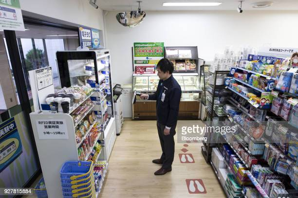 An employee uses a radiofrequency identification reader as he checks items on a shelf during a demonstration at a FamilyMart UNY Holdings Co...