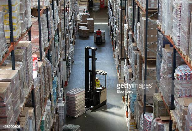 An employee uses a reach truck manufactured by Crown Equipment Corp to move products around a storage aisle in the food distribution center for OAO...